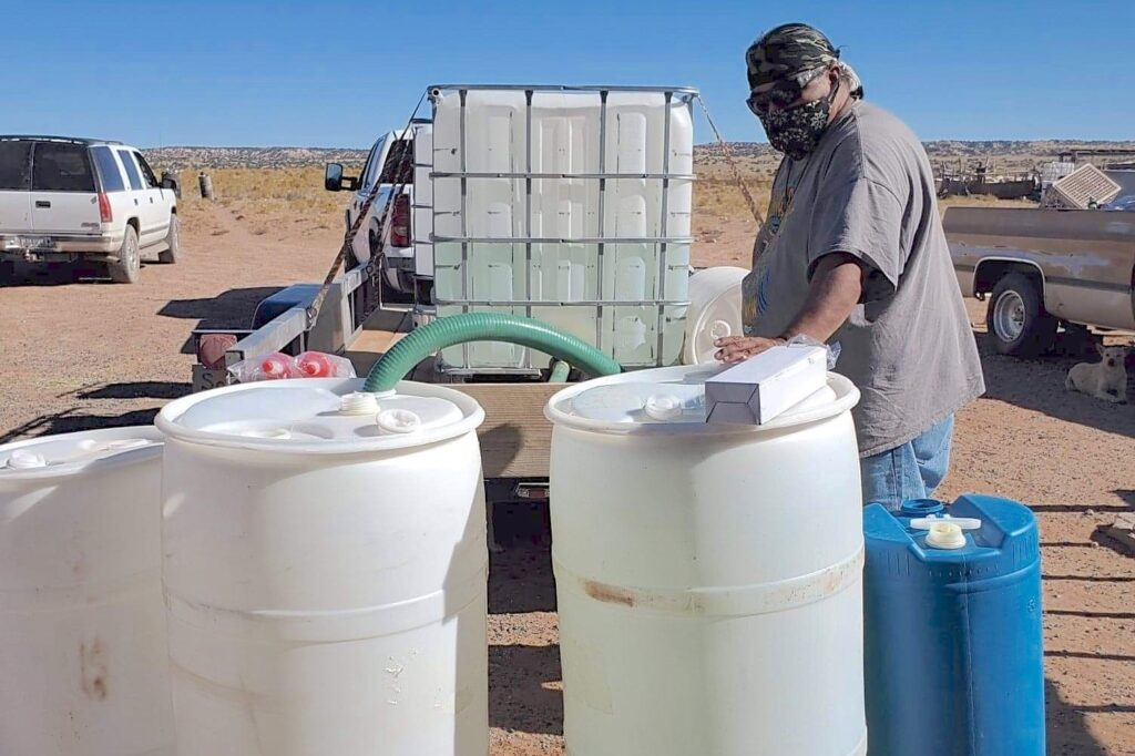 Photo of a person filling large plastic barrels with drinking water
